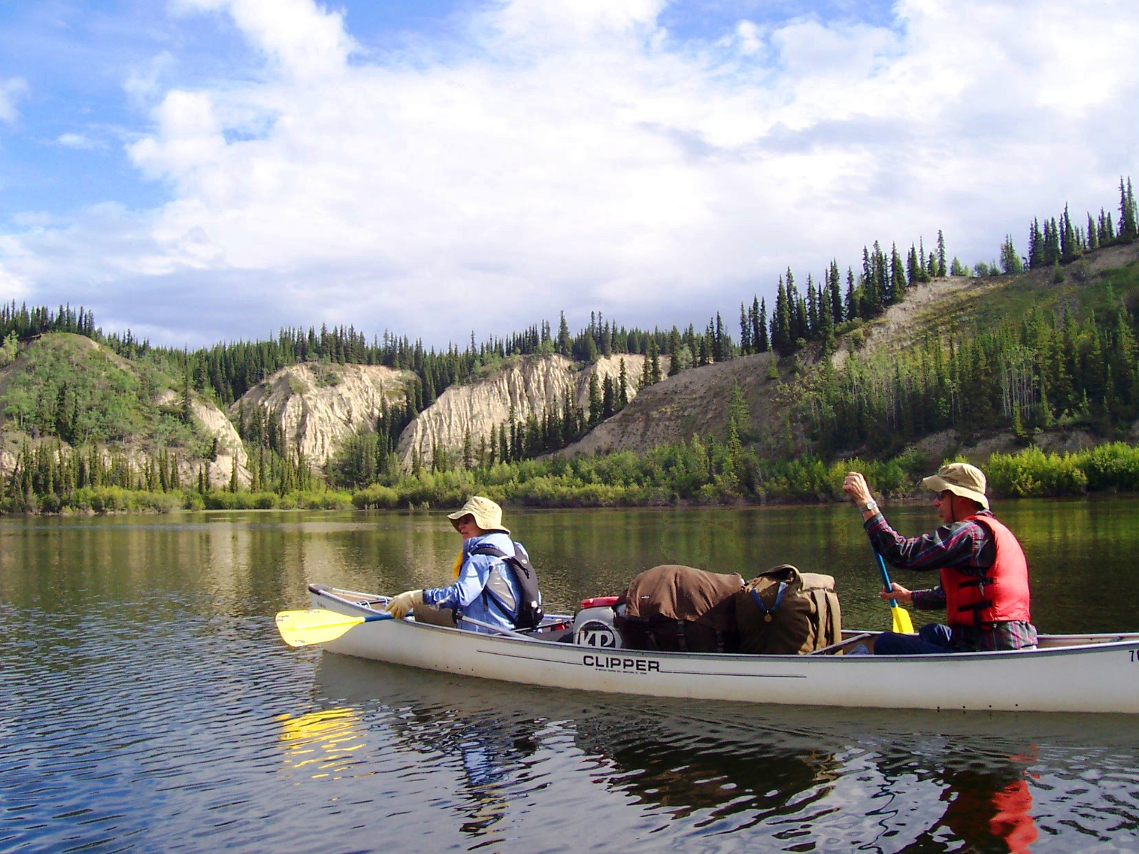 Two participants paddle a white Clipper canoe on Yukon's Big Salmon River.
